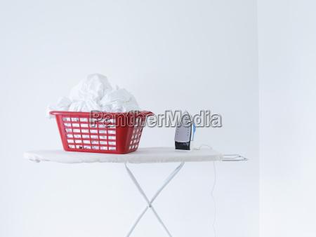 buegeleisen und waeschekorb auf buegelbrett gegen