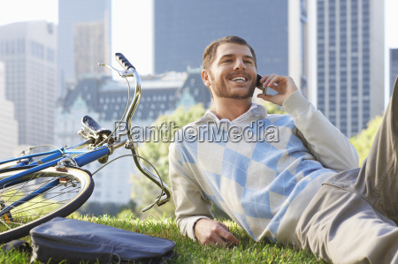 businessman using mobile phone by bicycle