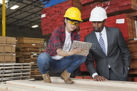 female industrial worker showing something on