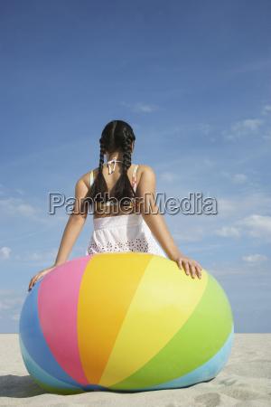 teenage girl sitting on beach ball