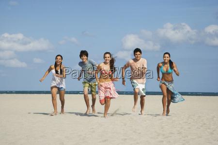 happy teenagers running on sandy beach