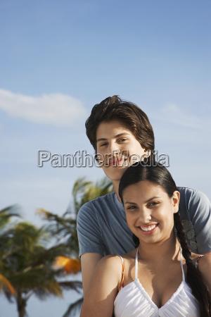 happy teenage couple on beach