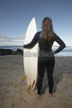 woman with surfboard standing on beach