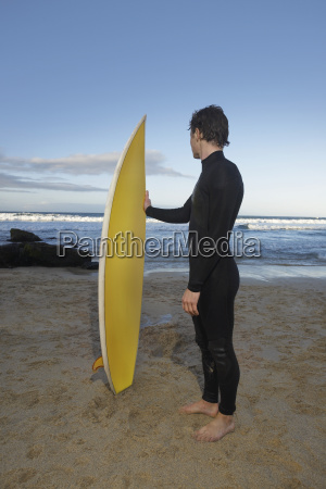 man with surfboard standing on beach