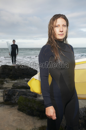 woman holding surfboard with male surfer