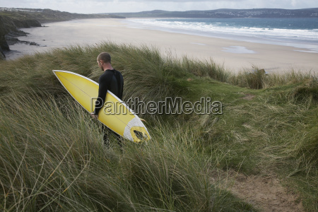 man with surfboard walking through grass