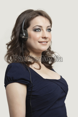 young woman wearing headphones against gray
