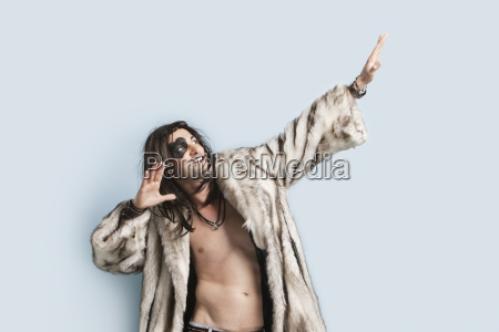young man in fur coat looking