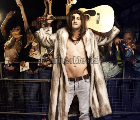 portraet junger rockmusiker mit gitarre posiert