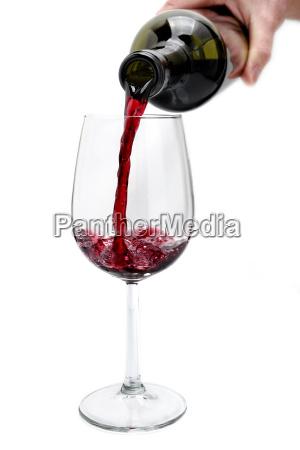 rotwein gegossen aus einer flasche in