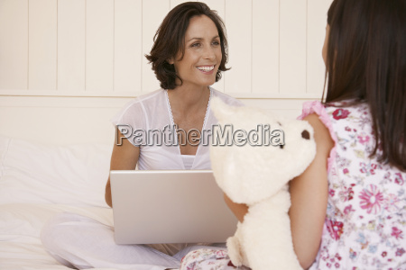mother with laptop looking at daughter