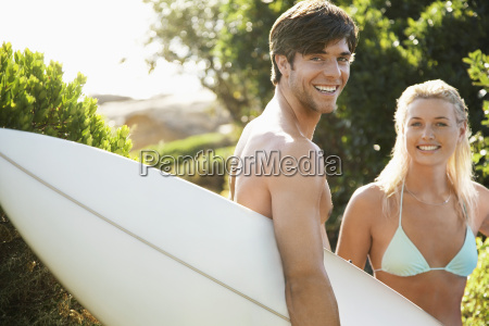 happy couple with surfboard at beach