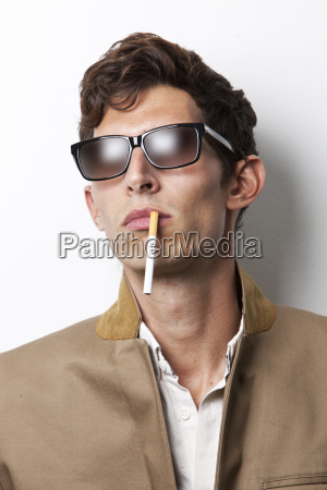 young man in sunglasses smoking cigarette