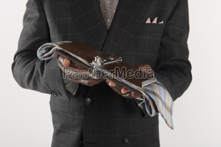 midsection of man holding tie press