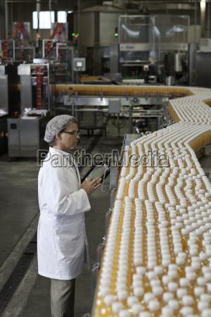mann kontrolliert orangensaftflaschen bei abfuellanlage