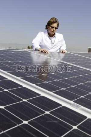 mann der unten auf solarenergieverkleidungen schaut