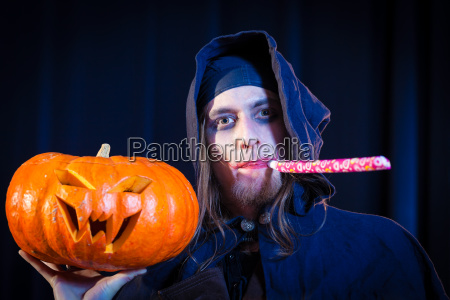 mann in furchtsamen halloween kostuem haelt