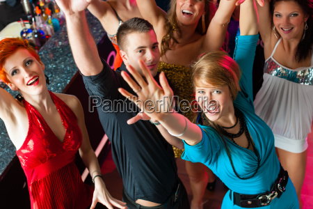 young people dancing in club or