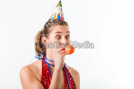 woman celebrating birthday blowing up balloon