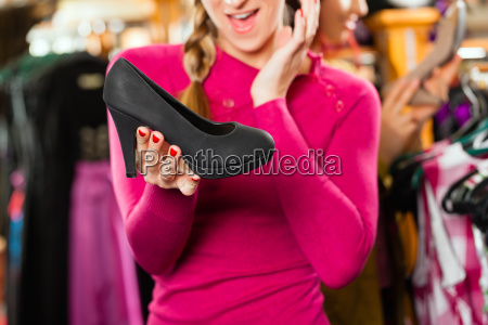 woman is buying shoes for her