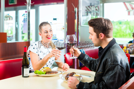 friends or couple eating and drinking