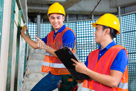 asian worker controlling building on construction