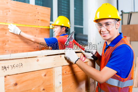 worker close a wood box with