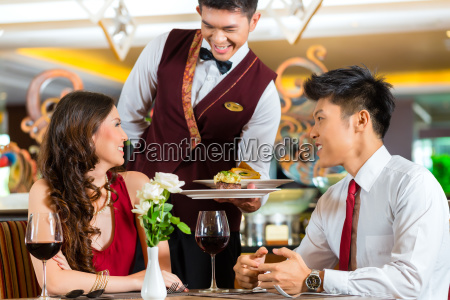 chinese waiter serving dinner in elegant