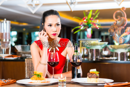 young asian woman sitting in restaurant
