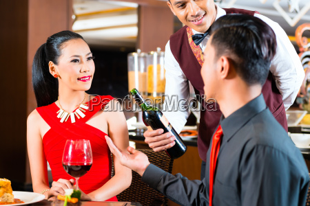 young asian couple drinking wine in