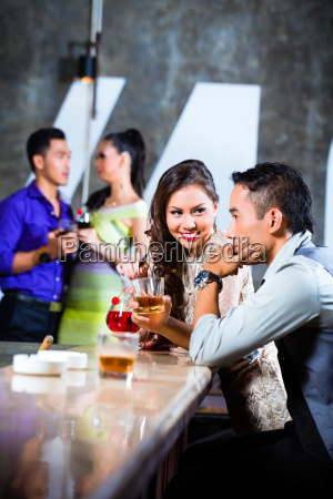 asian couples flirting and drinking at