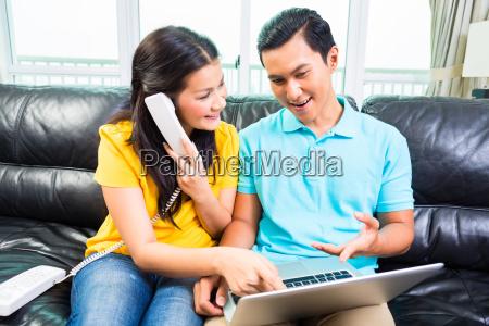 asiatisches ehepaar ruft die kostuemhotline an