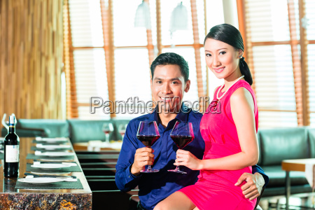 asian couple with glass of red