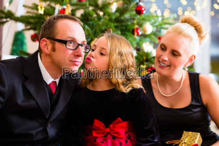 parents and daughter with christmas gifts