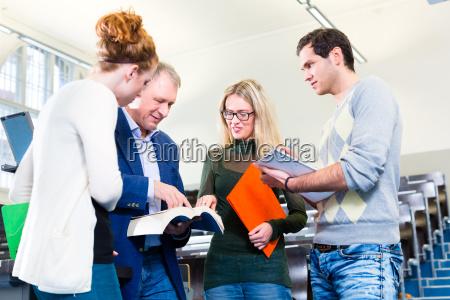 students asking professor in college auditorium
