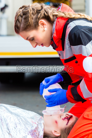ambulance doctor giving oxygen to female