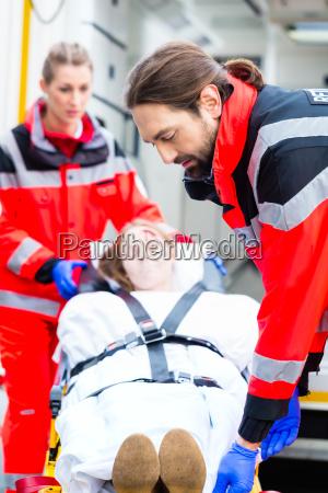 ambulance helping injured woman on stretcher