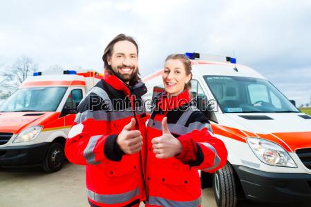 notarzt und sanitaeter mit krankenwagen