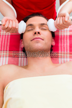 man having face massage in wellness