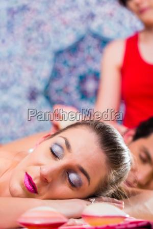 couple having sea shell massage in