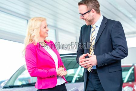 woman buying new car in dealership