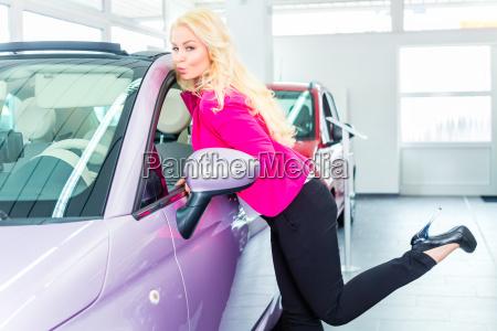 woman choosing new car at dealership