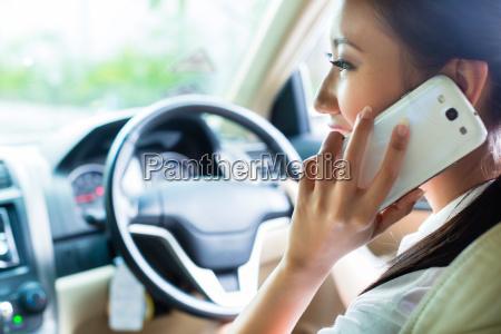 asian woman using phone driving car