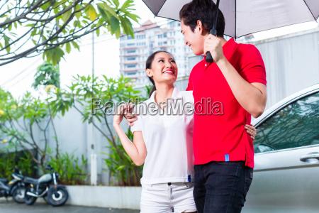 asian couple walking with umbrella through