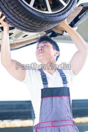 asian chinese car mechanic changing auto