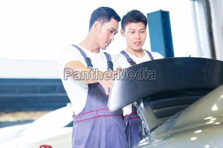 car mechanics looking under hood of