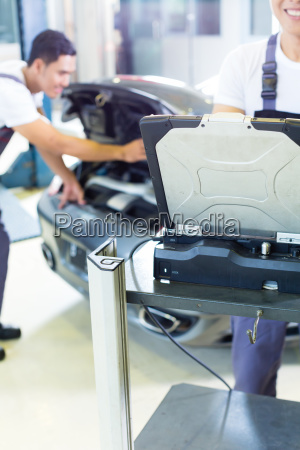car mechanics with diagnosis tool in