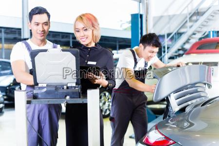 car mechanic team with diagnosis tool