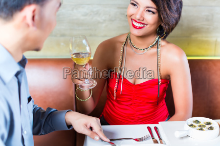 asian couple clinking wine glasses in