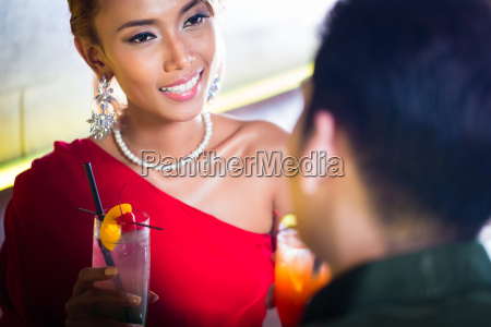 asian couple drinking cocktails in fancy